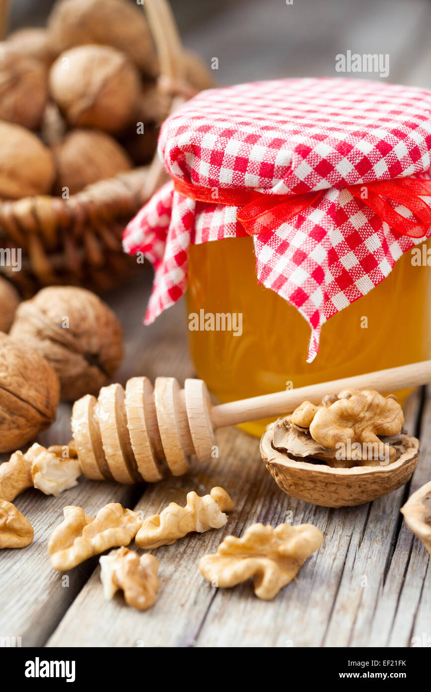 Honey in jar, walnut in basket on background on old kitchen table - Stock Image