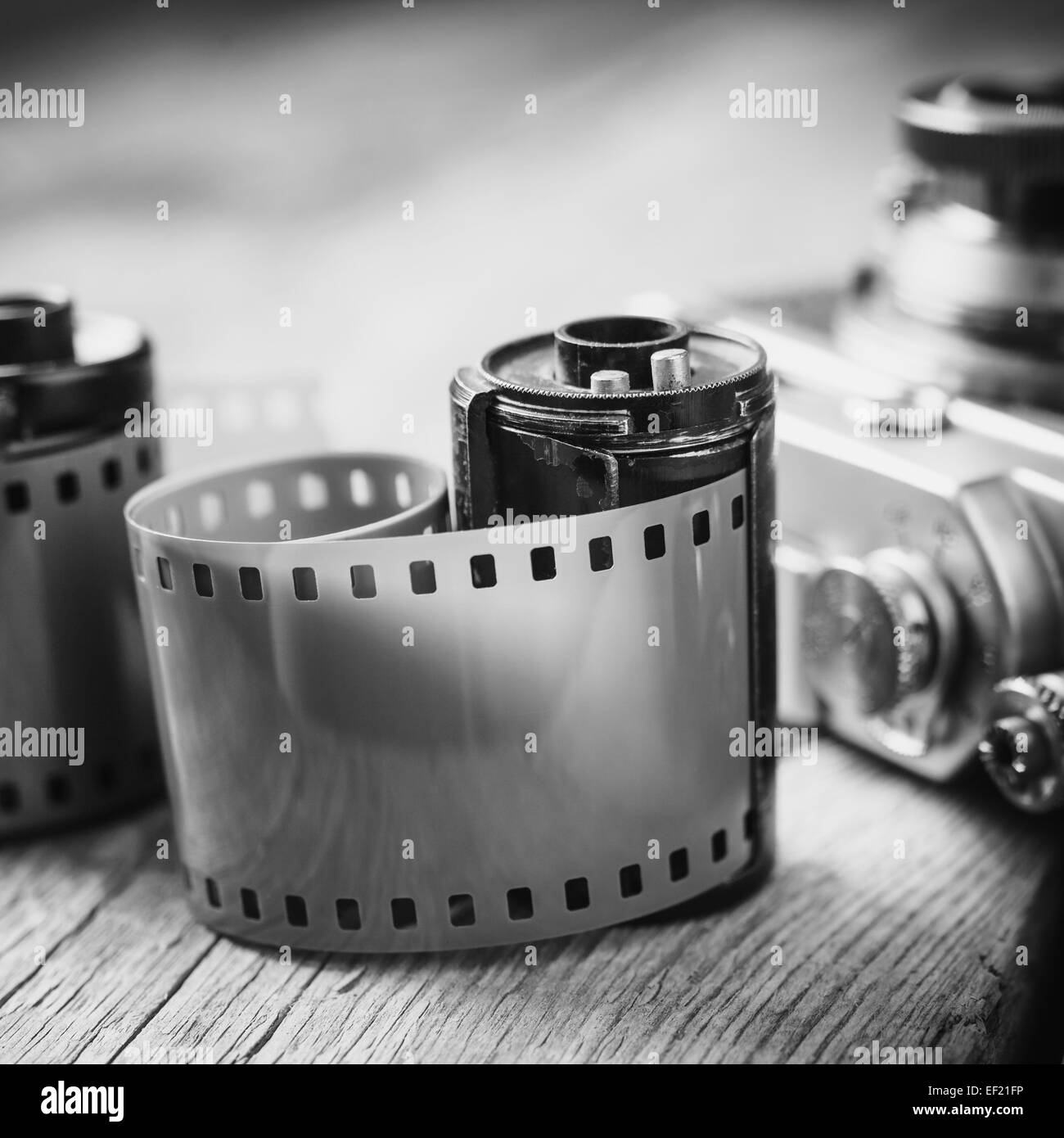 Old photo film cassette and retro camera on background. Vintage black and white stylized. - Stock Image