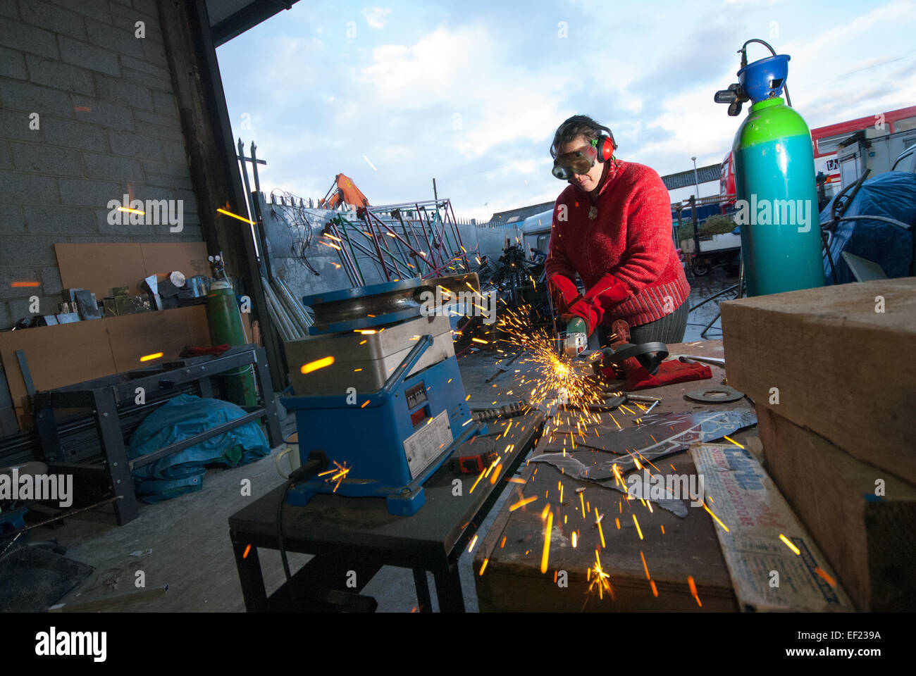 A female welder using an angle grinder - Stock Image