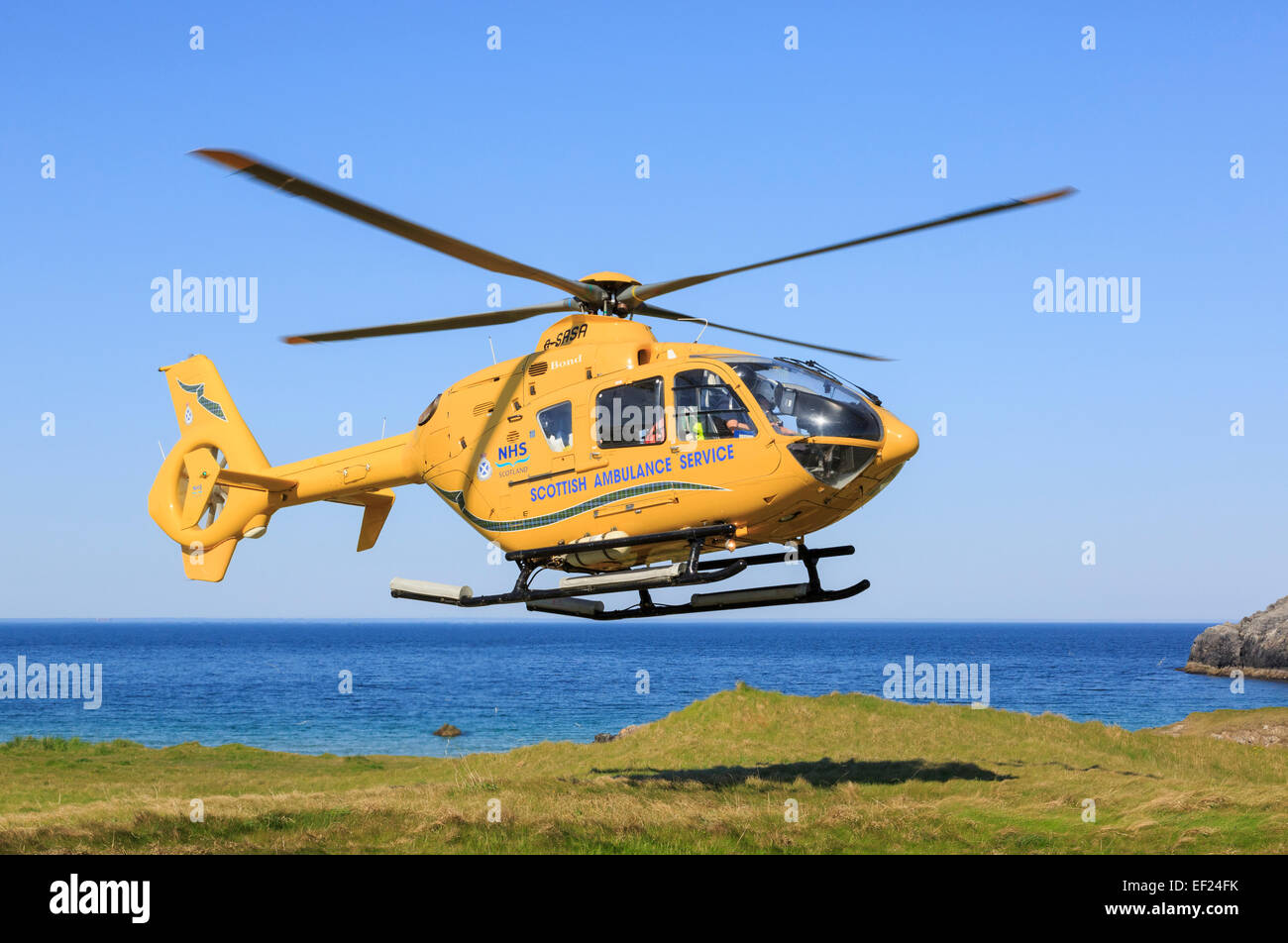 Scottish Air Ambulance Service Helicopter taking off after a rescue mission on remote North West Highlands coast. - Stock Image