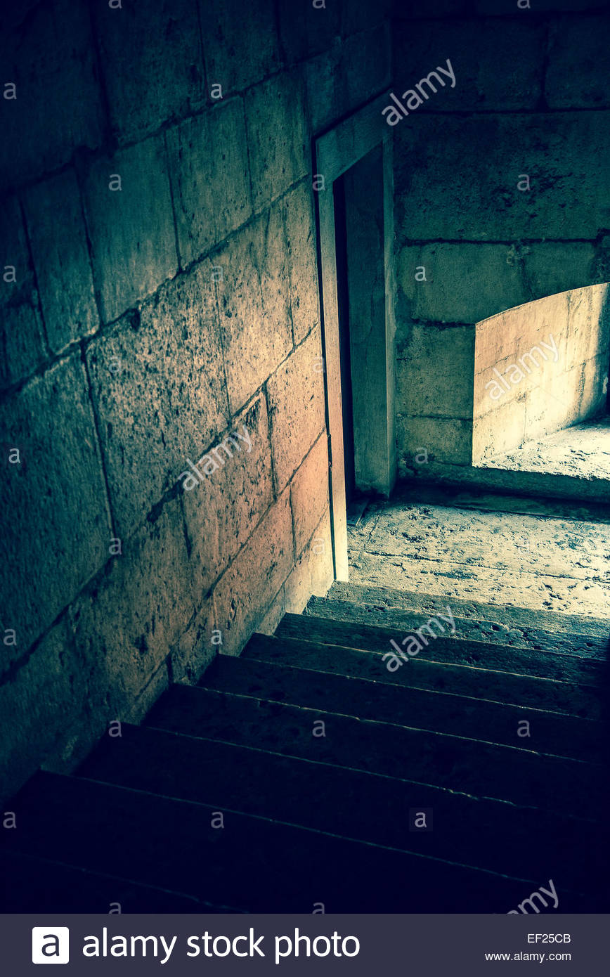 Descending staircase in stone tower and window light - Stock Image