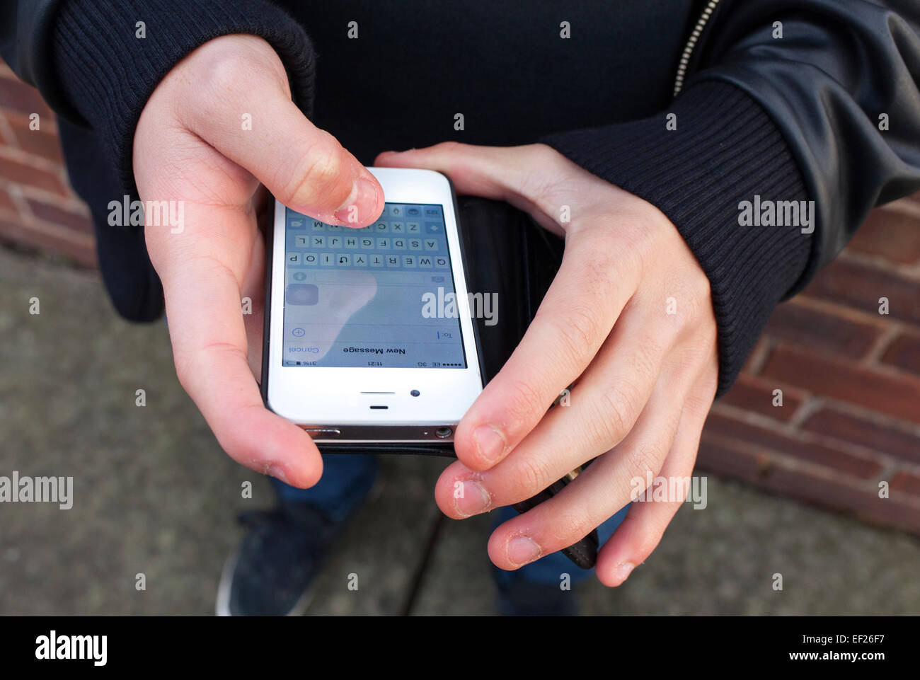 A teenager using an iPhone to send a text message in the U.K. - Stock Image