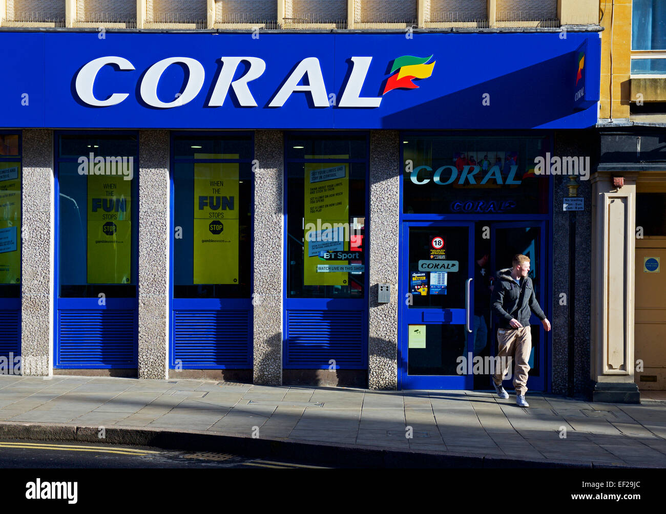 Man walking out of branch of Corals bookmakers, Northampton, Northamptonshire, England UK - Stock Image