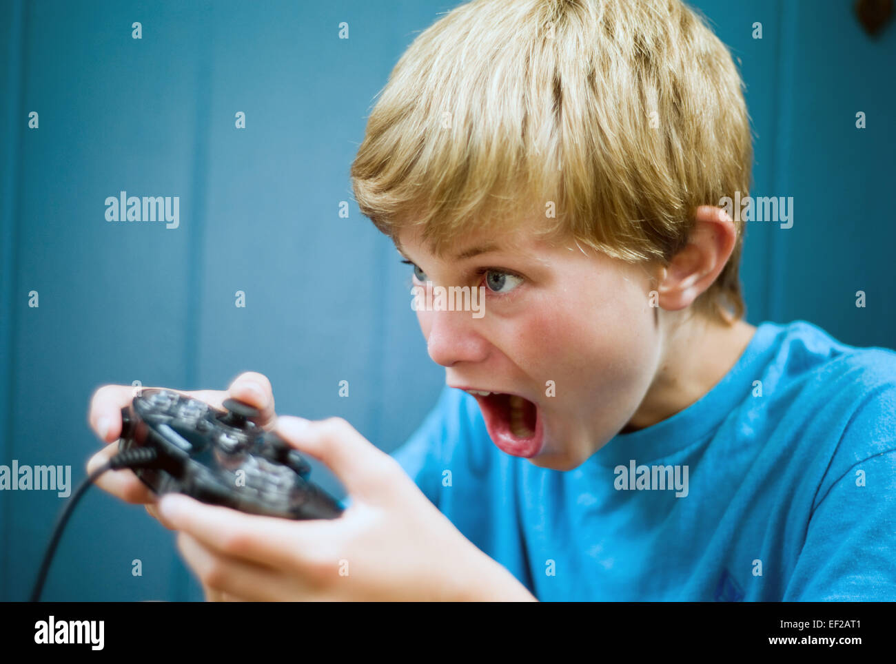 Young boy, 10-11-12-13, playing video game using controller with concentration - Stock Image