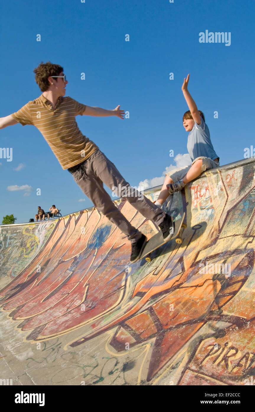 A young man and boy skateboarding at a skatepark - Stock Image