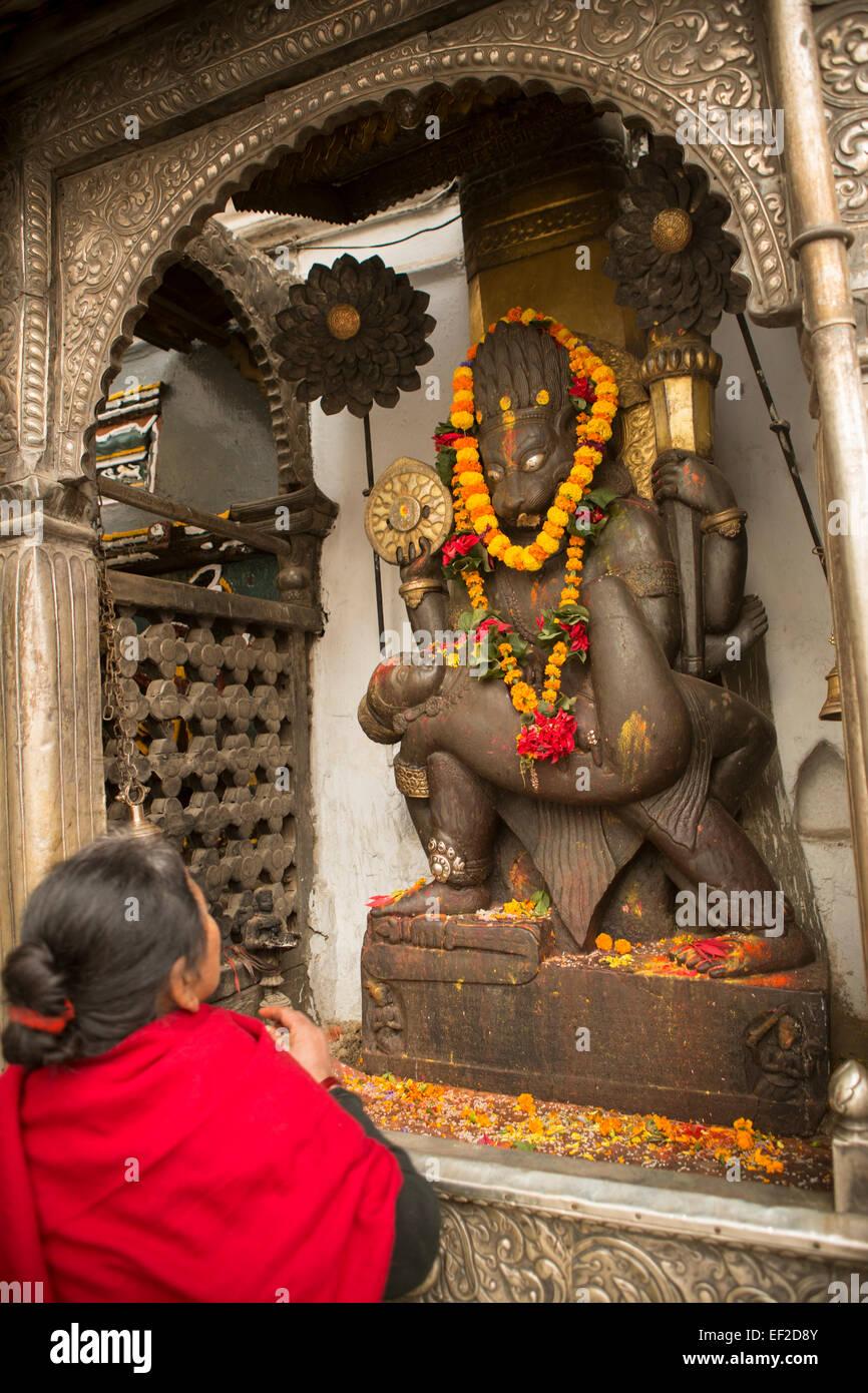 Woman praying to a god in Kathmandu's Durbar Square, Nepal. - Stock Image