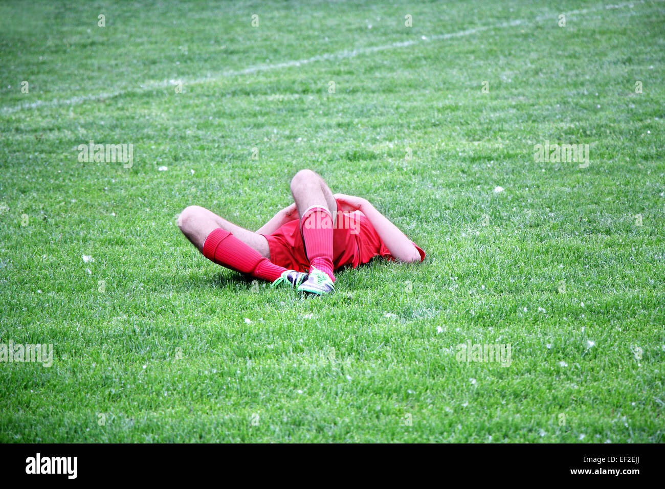 Injured Football or Soccer Player Lying On The Ground - Stock Image
