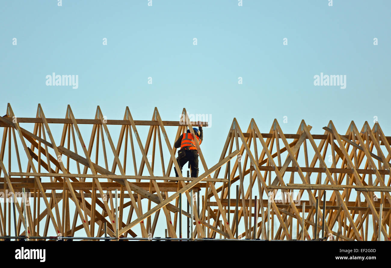 Worker assembling roof for new home build - Stock Image