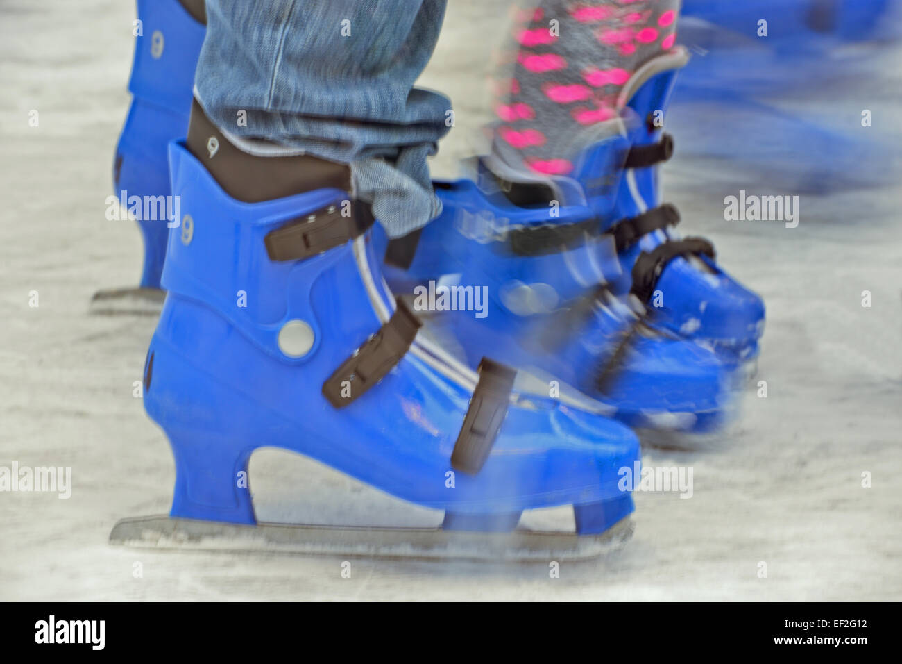 Blurred lower body shoot of Mother and child ice skaters on out door ice rink - Stock Image