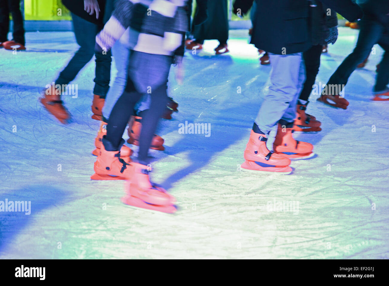 Blurred lower body shoot of ice skaters on out door ice rink - Stock Image
