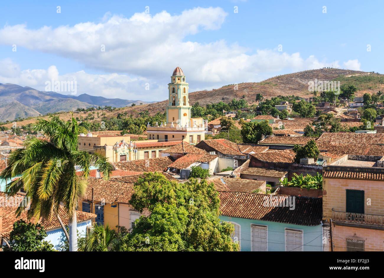 Panoramic landscape: terracotta tiled rooftop view over Trinidad, Cuba with Iglesia Parroquial de la Santísima - Stock Image