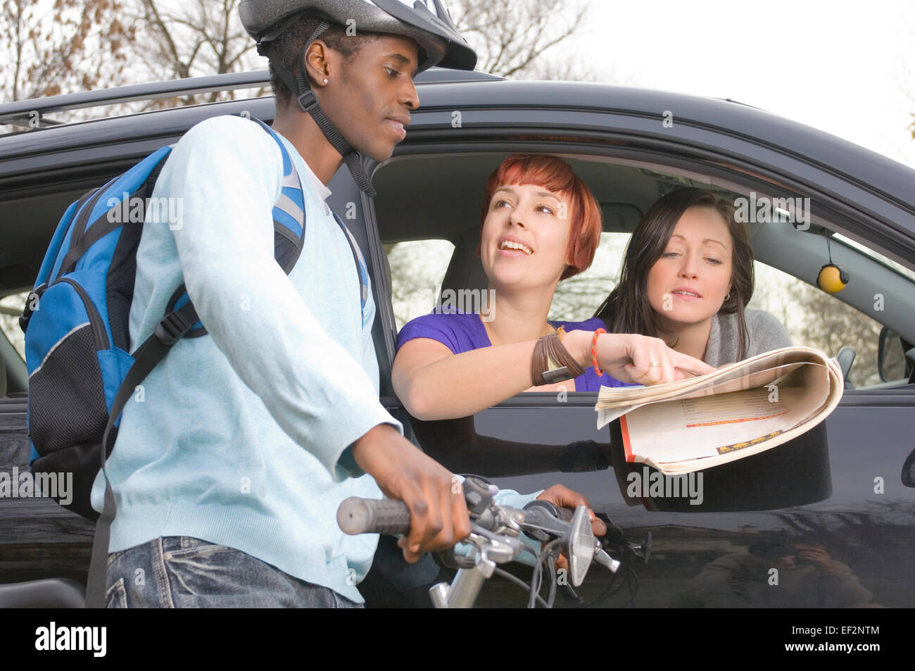 Two women in car asking cyclist for directions Stock Photo