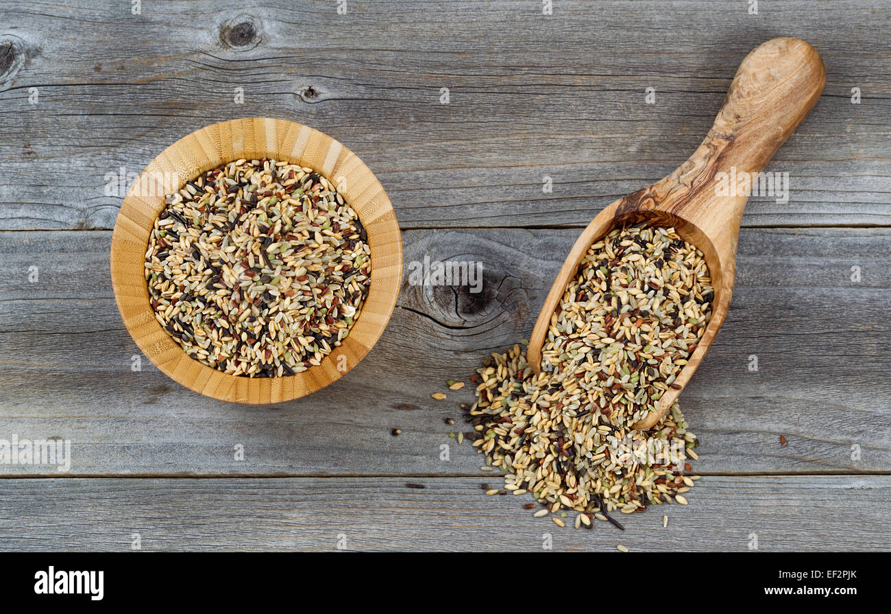 Top view angled shot of a wooden bowl and scoop filled with whole grain rice on rustic wood. - Stock Image