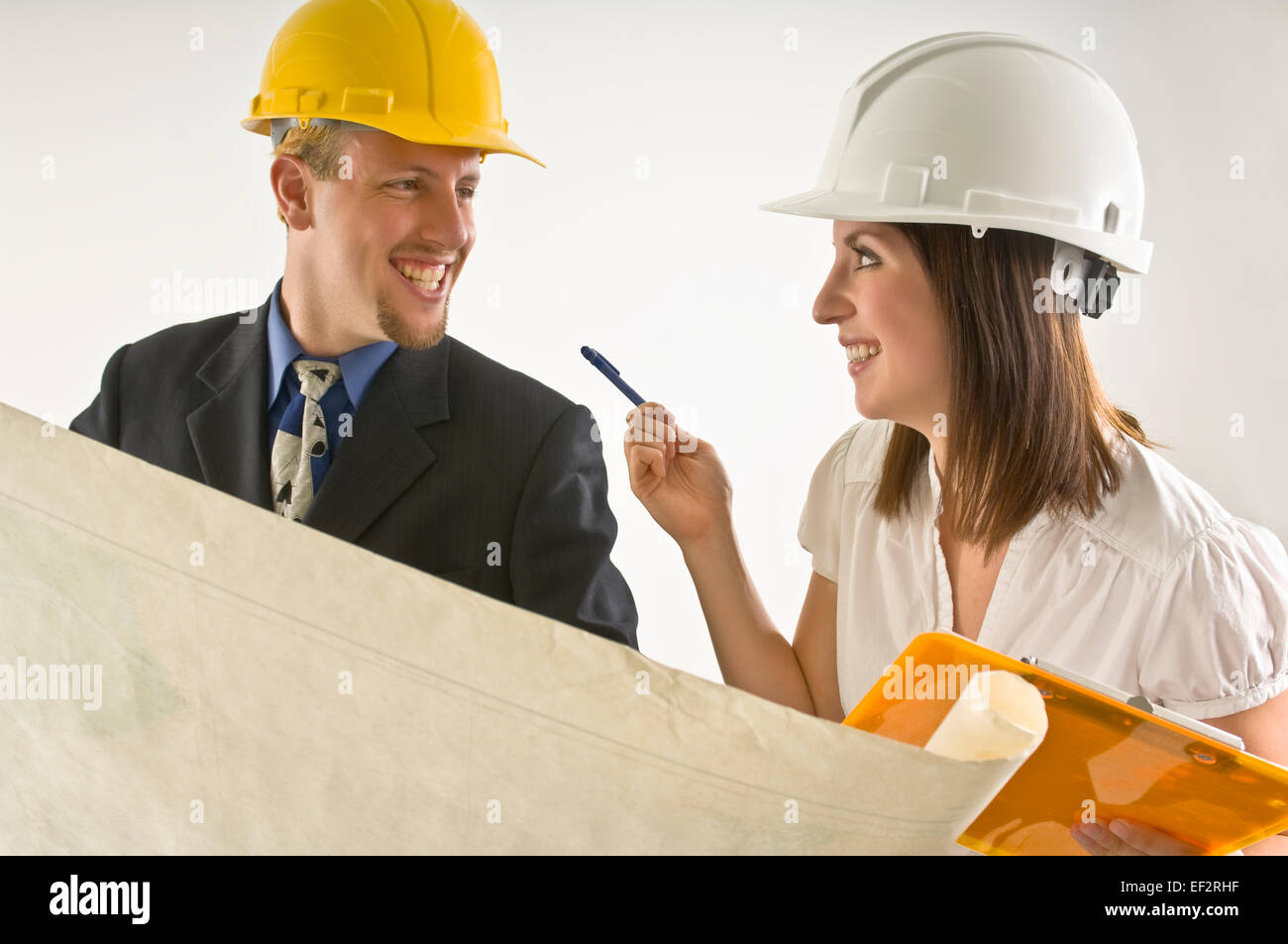 Two happy architects looking at blueprints Stock Photo