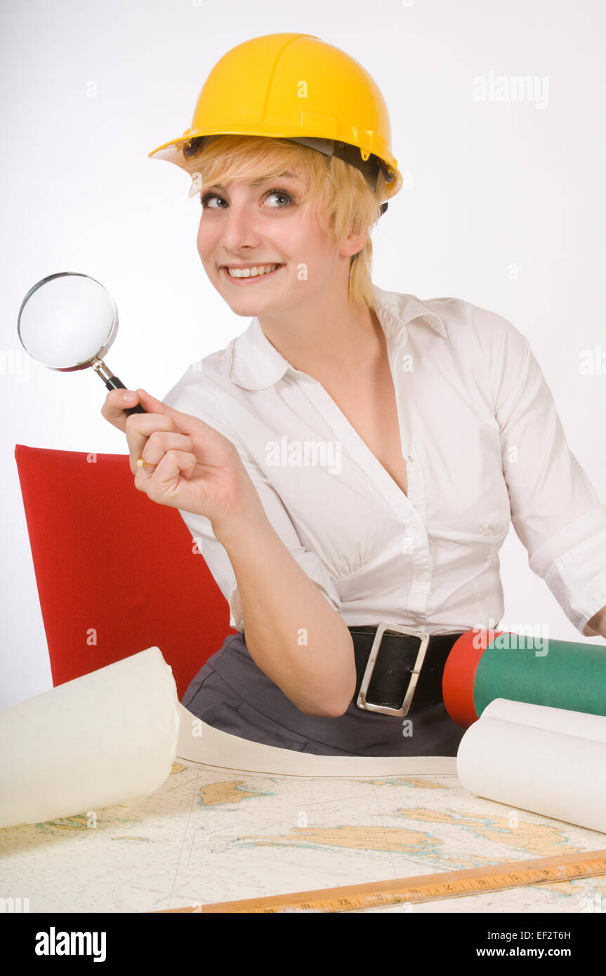 Woman holding magnifying glass while looking at map - Stock Image