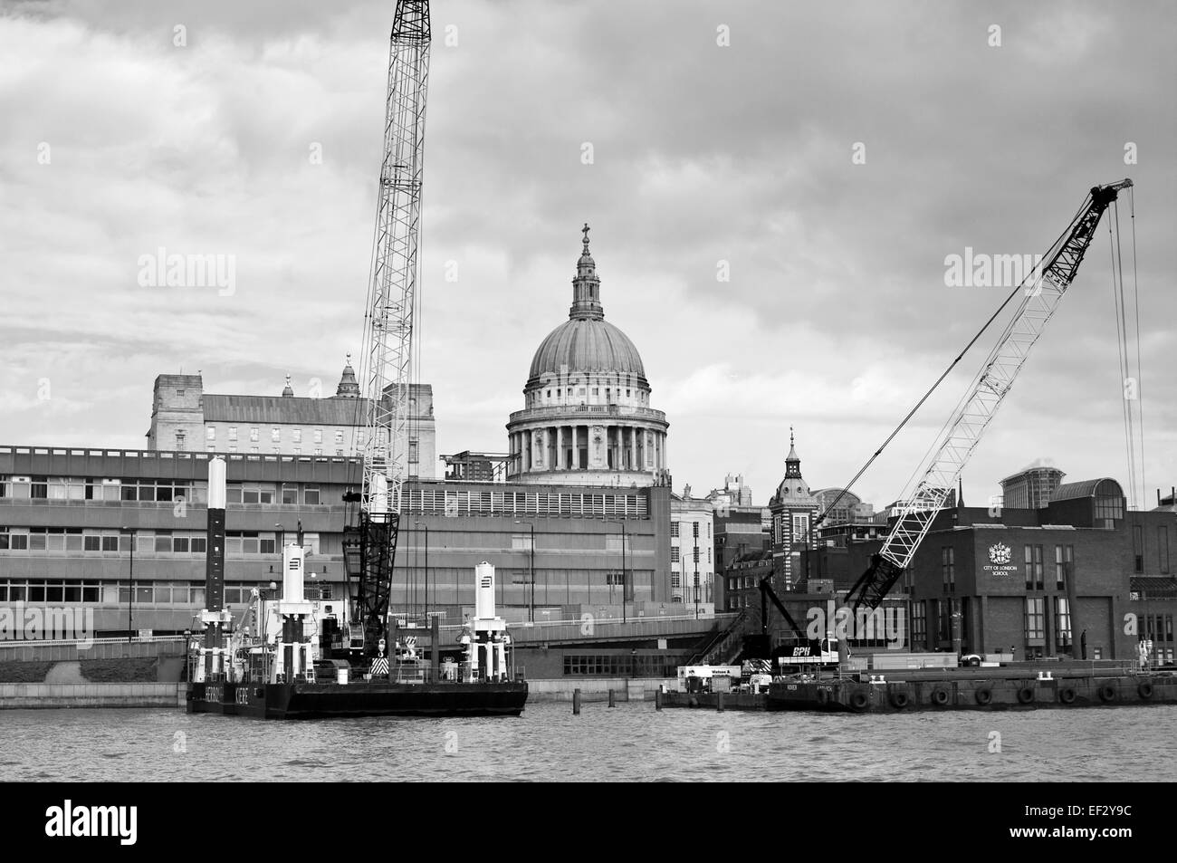Black and white view of St Paul's Cathedral framed by two floating cranes, seen from the River Thames, London, England Stock Photo