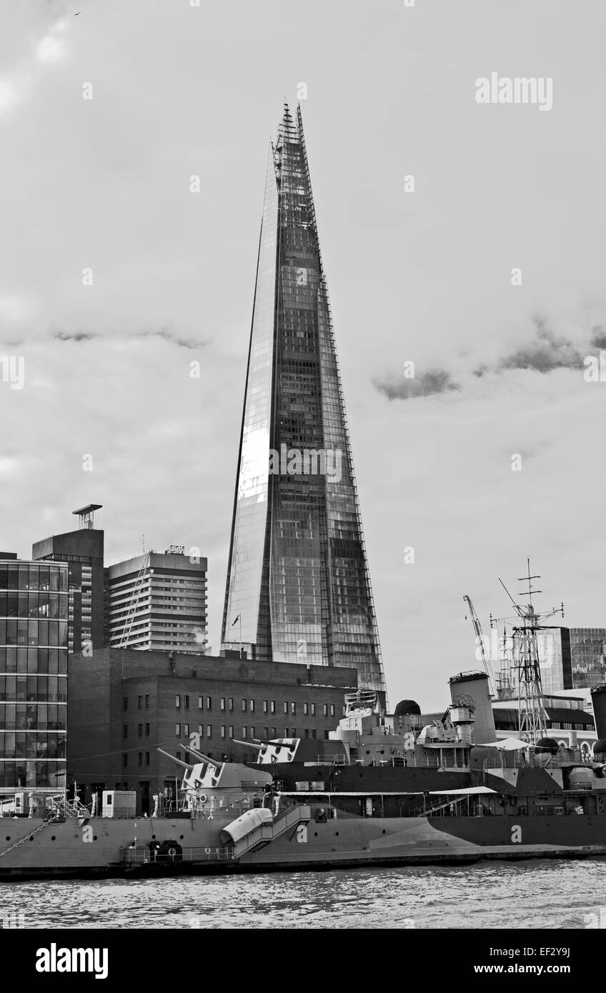 Black and white view of the Shard, HMS Belfast moored in the foreground, seen from the River Thames, central London, Stock Photo
