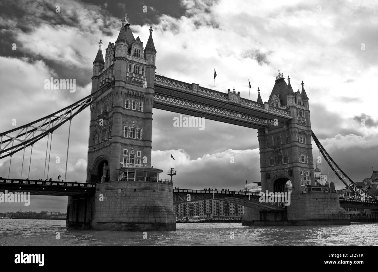 Dramatic black and white view of Tower Bridge against cloudy sky, seen from the River Thames, central London, England - Stock Image
