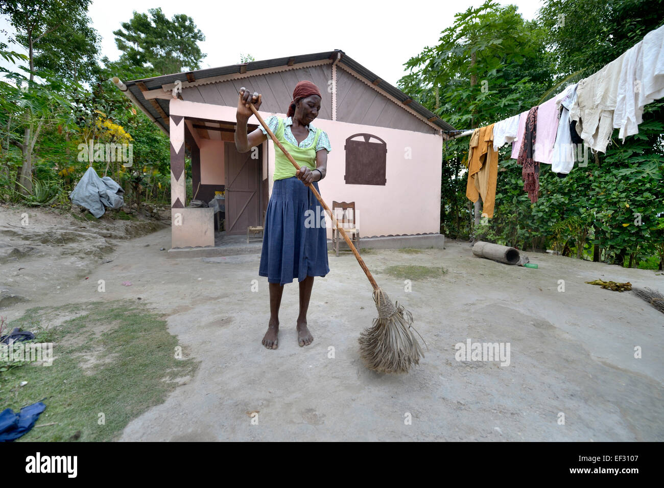 Elderly woman sweeping the courtyard in front of the house which she received from a relief organisation after the - Stock Image
