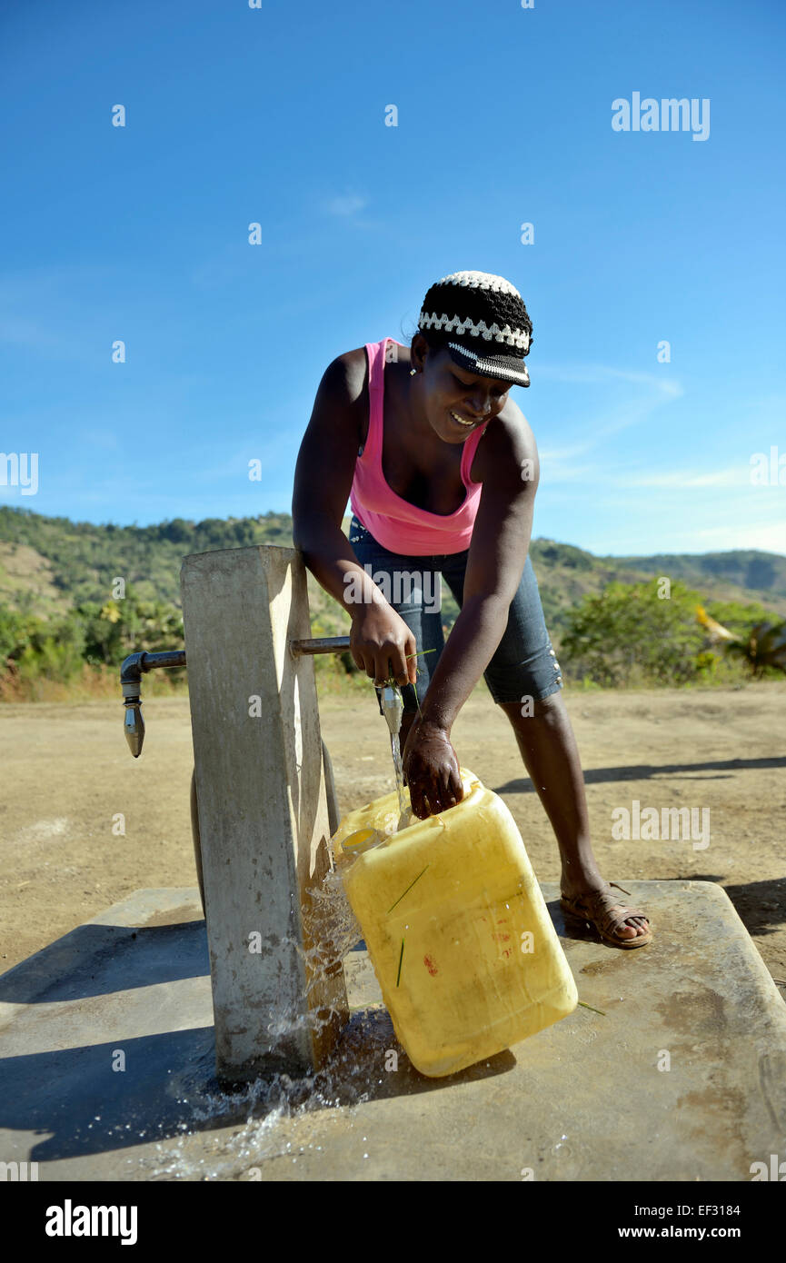 Young woman filling a canister at a water supply well, Ridore, La Vallee, Sud-Est Department, Haiti - Stock Image