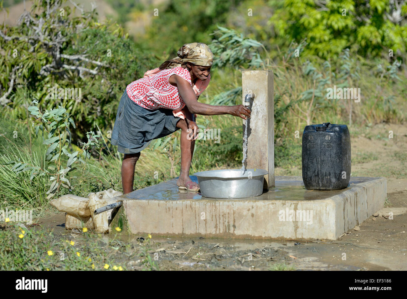 Elderly woman at a water supply well, Ridore, La Vallee, Sud-Est Department, Haiti - Stock Image