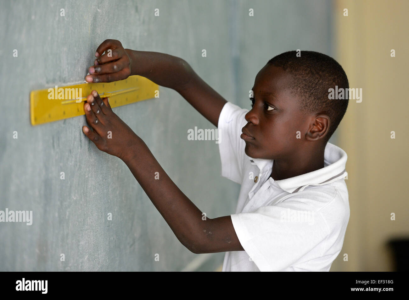 Pupil, 10 years, solving a geometry assignment at the blackboard, Basile Moreau School, Carrefour, Port-au-Prince - Stock Image