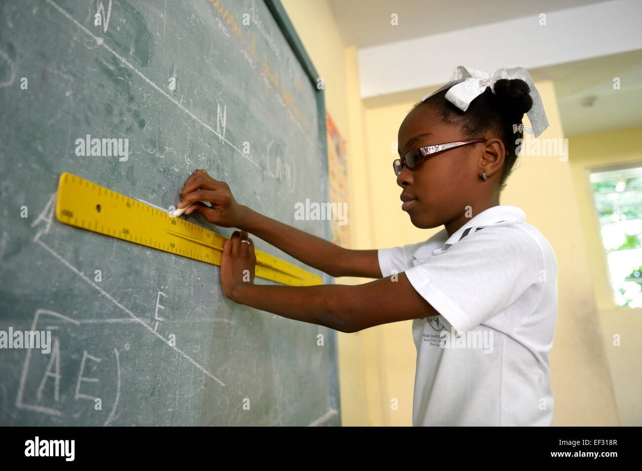 Schoolgirl, 10 years, solving a geometry assignment at the blackboard, Basile Moreau School, Carrefour, Port-au - Stock Image