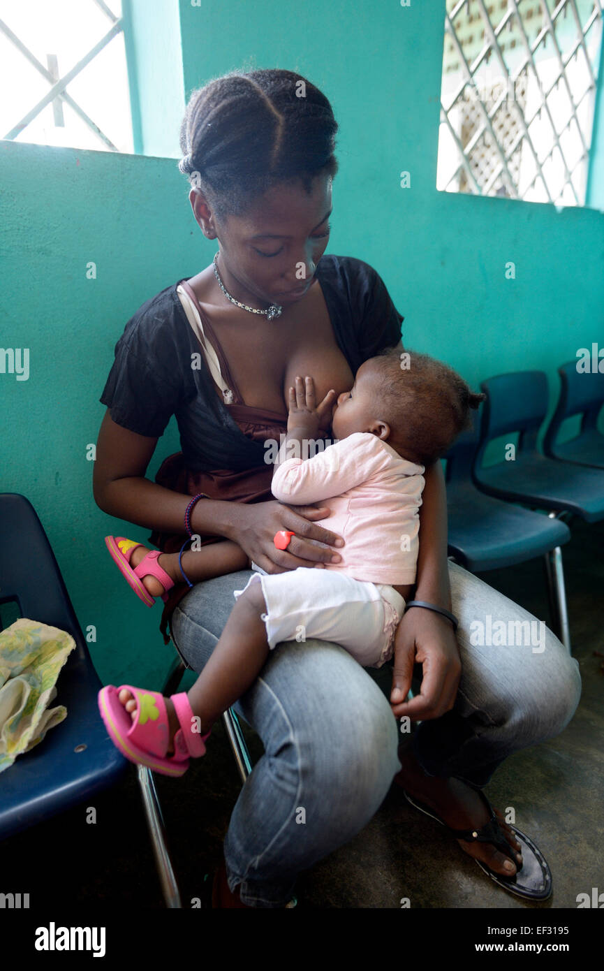 Young mother, 21 years, nursing her daughter, 7 months, kindergarten of the Salesian project Lakou, district of - Stock Image