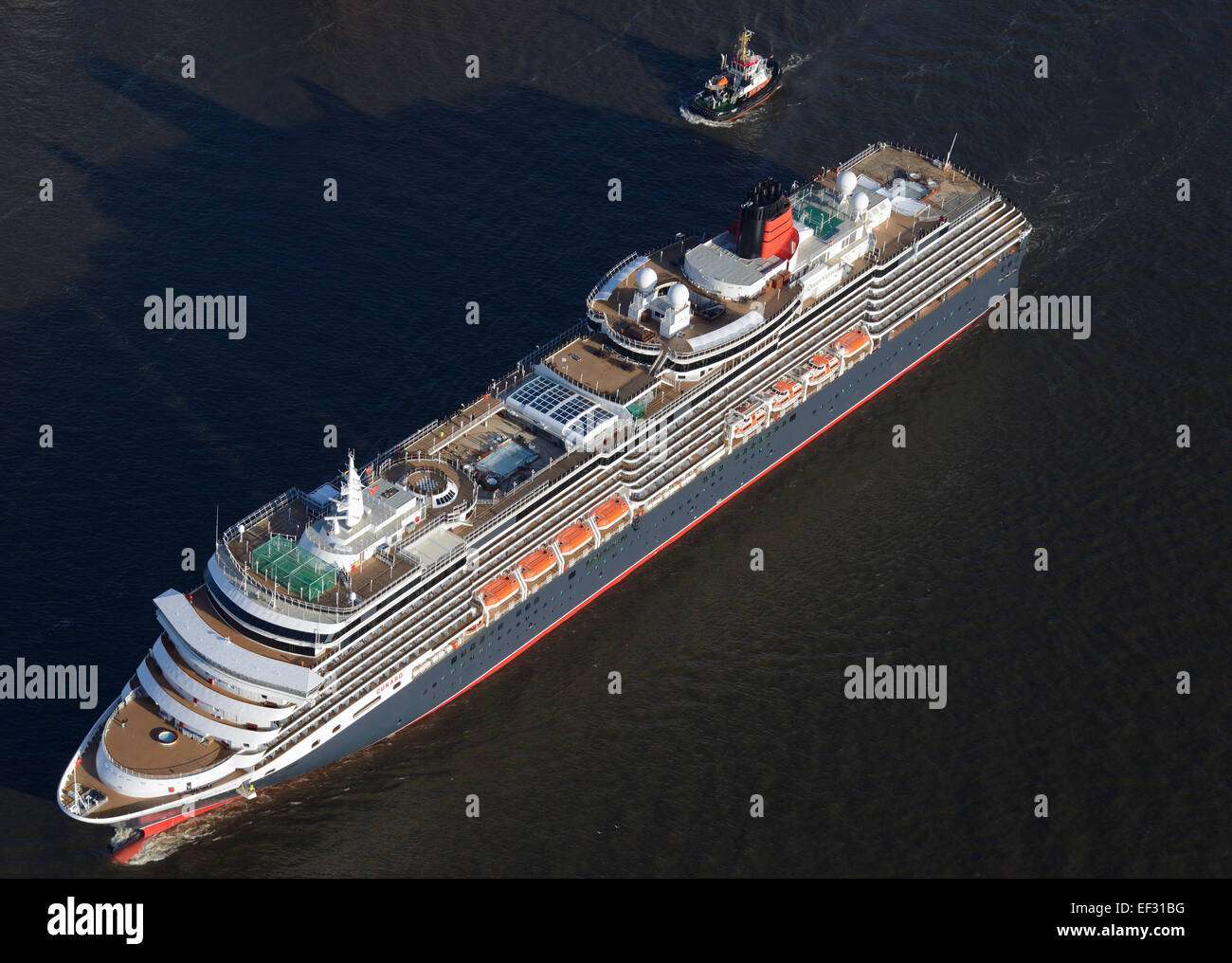 Cruise ship Queen Victoria, accompanied by a small tugboat, Hamburg, Germany - Stock Image
