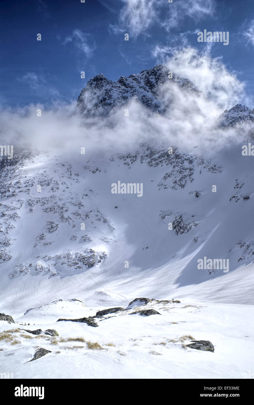 Picturesque view of sun illuminating snowy slopes in high mountains - Stock Image