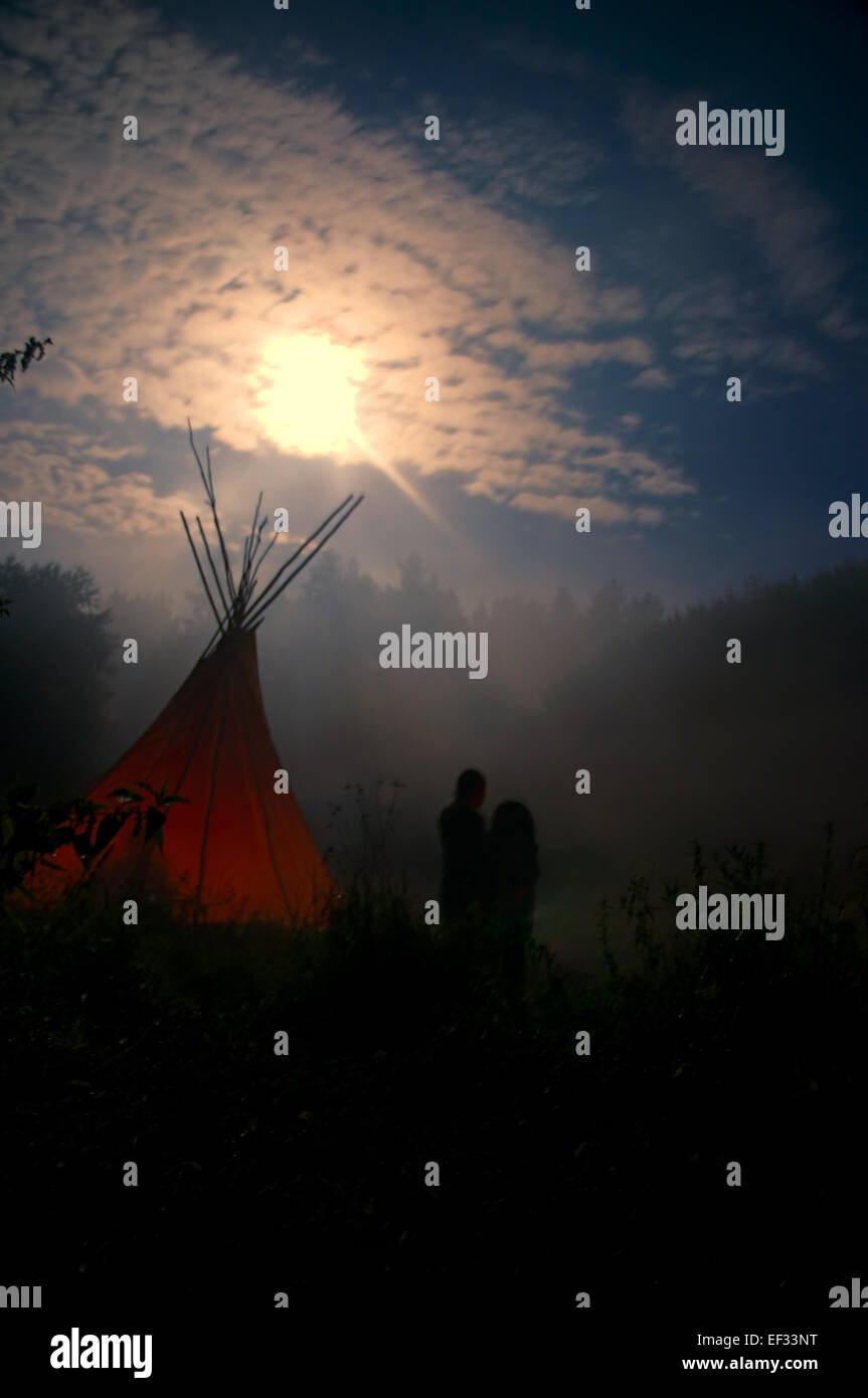 Couple standing outside in the mystical darkness lit by moonlight - Stock Image