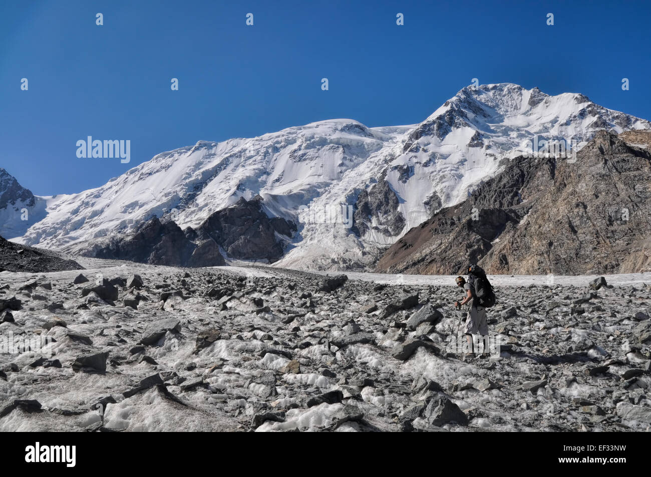 Young adventurer with backpack on glacier below snow-covered highest peaks in Tien-Shan mountain range in Kyrgyzstan - Stock Image