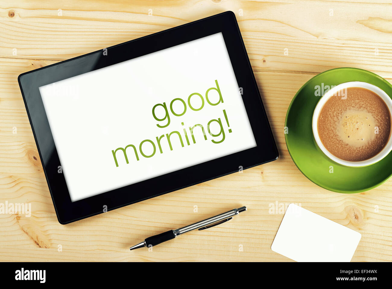 Good Morning Message on Tablet Computer Screen on Office Table. - Stock Image