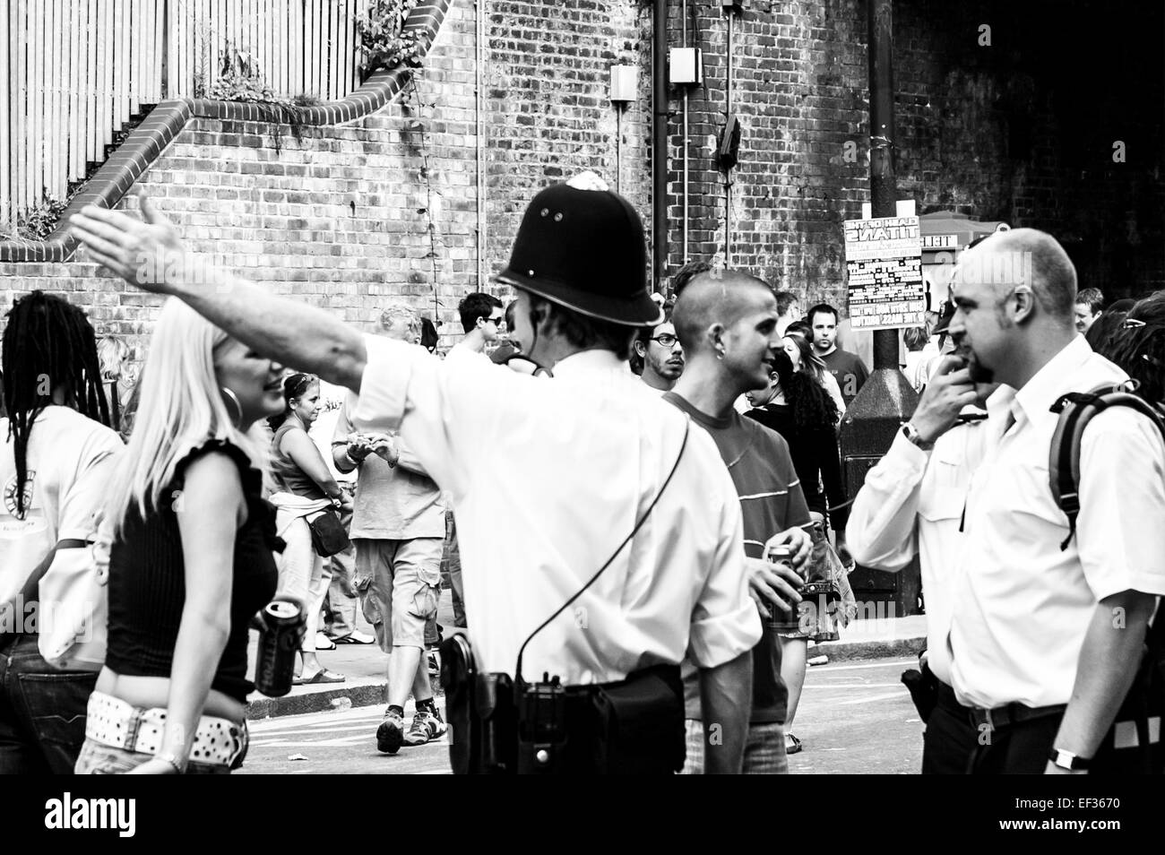 LONDON, UK- August 28th 2005: At the Notting Hill Carnival, policeman with his arm up shows direction to member - Stock Image