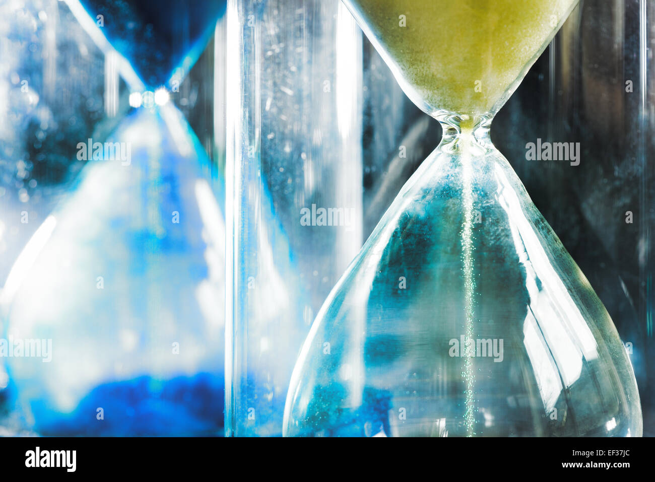 timer hourglass streaming grains of sand flowing through depicting things are running out - Stock Image