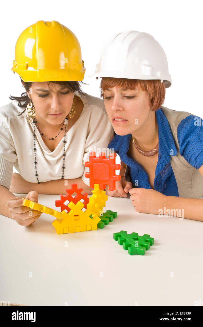Two women playing with child's building toy - Stock Image