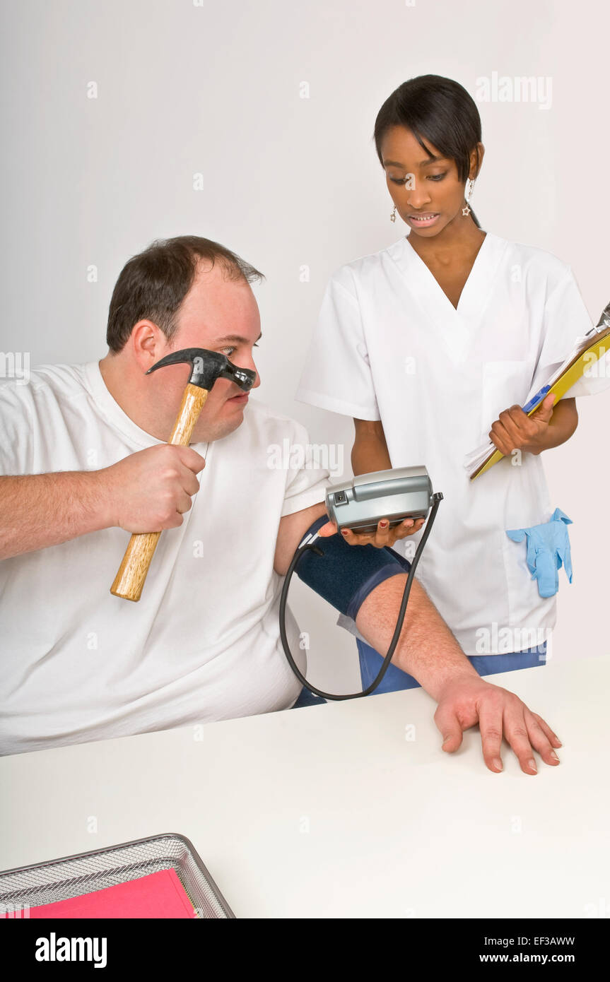 Patient about to hit blood pressure monitor with a hammer - Stock Image