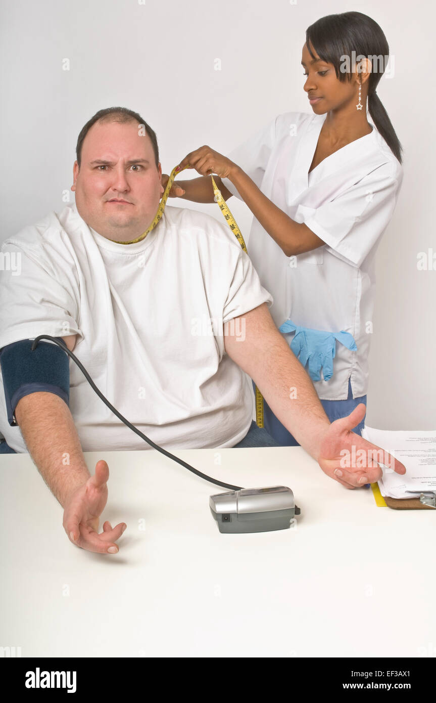 Nurse measuring patient's neck circumference - Stock Image