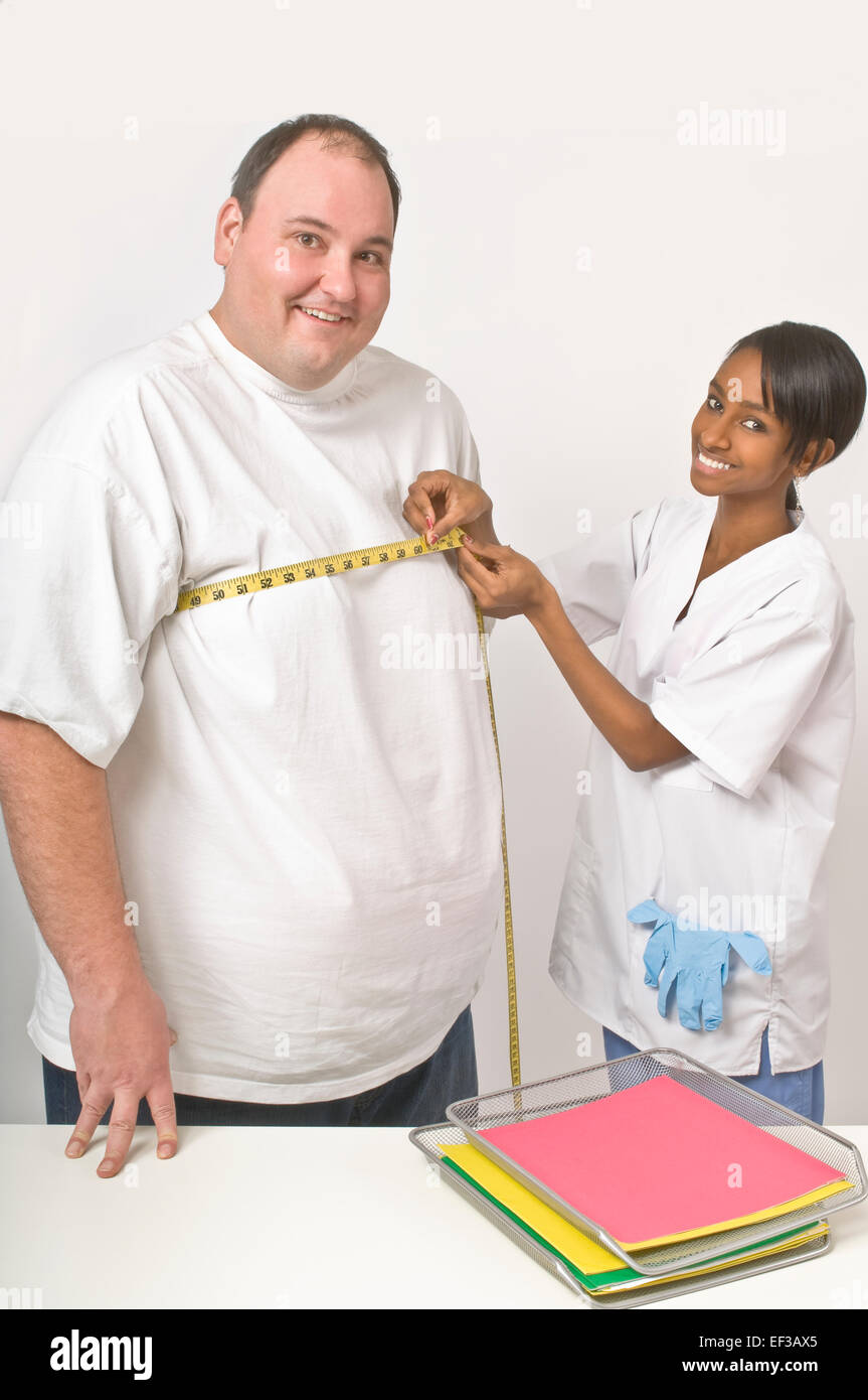 Nurse measuring overweight man - Stock Image