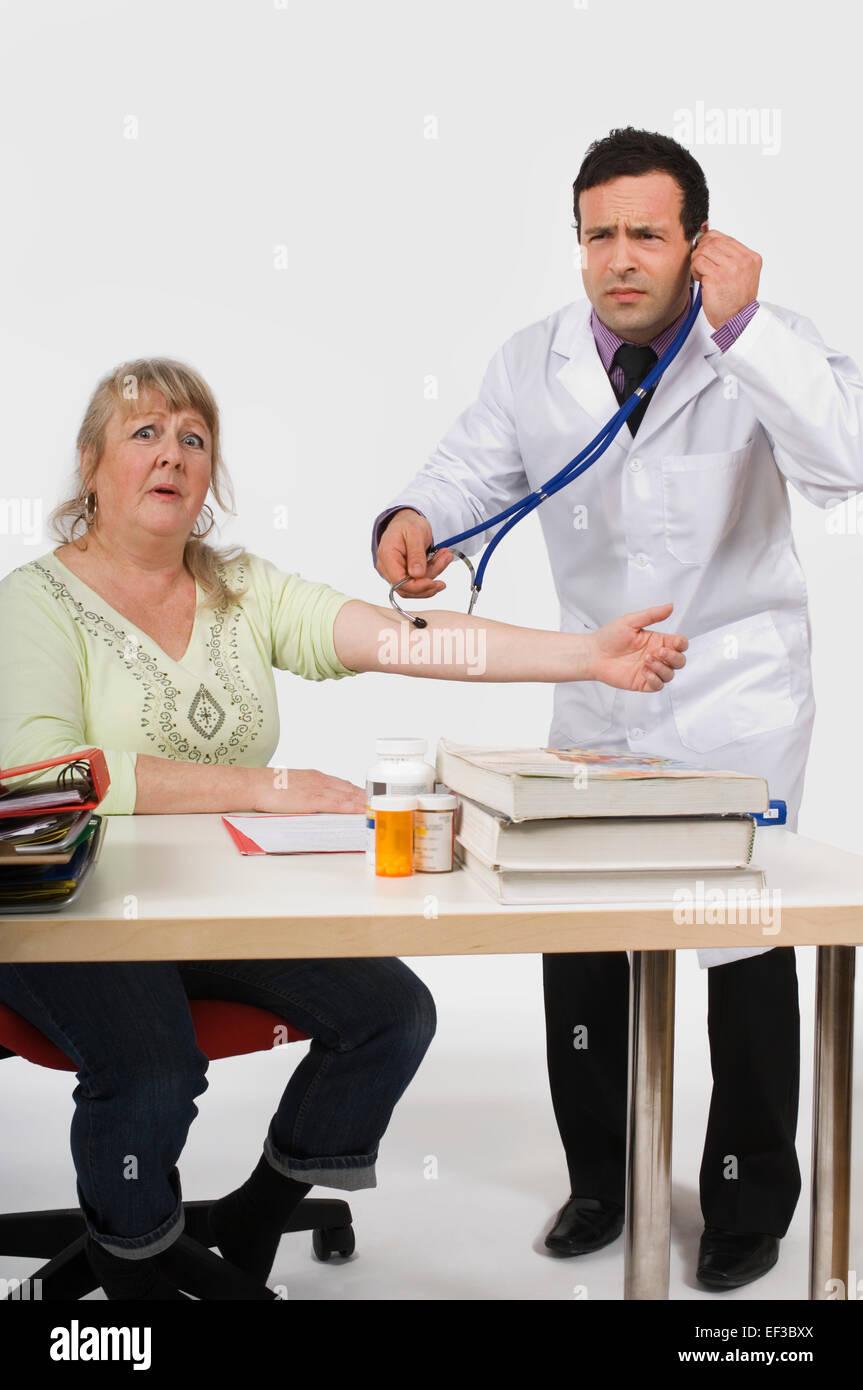 Doctor using stethoscope incorrectly - Stock Image