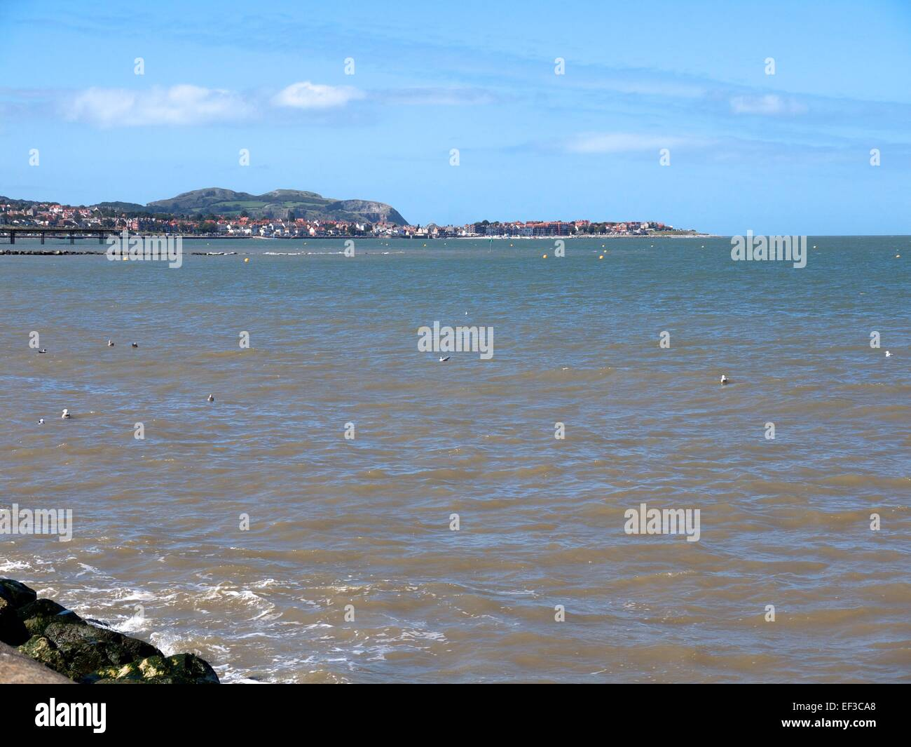 Rhos on Sea in the distance and the sea in the foreground - Stock Image
