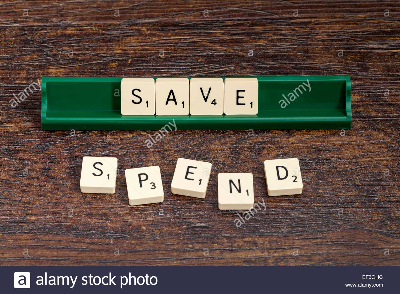 Save and Spend spelled out with scrabble letters. - Stock Image