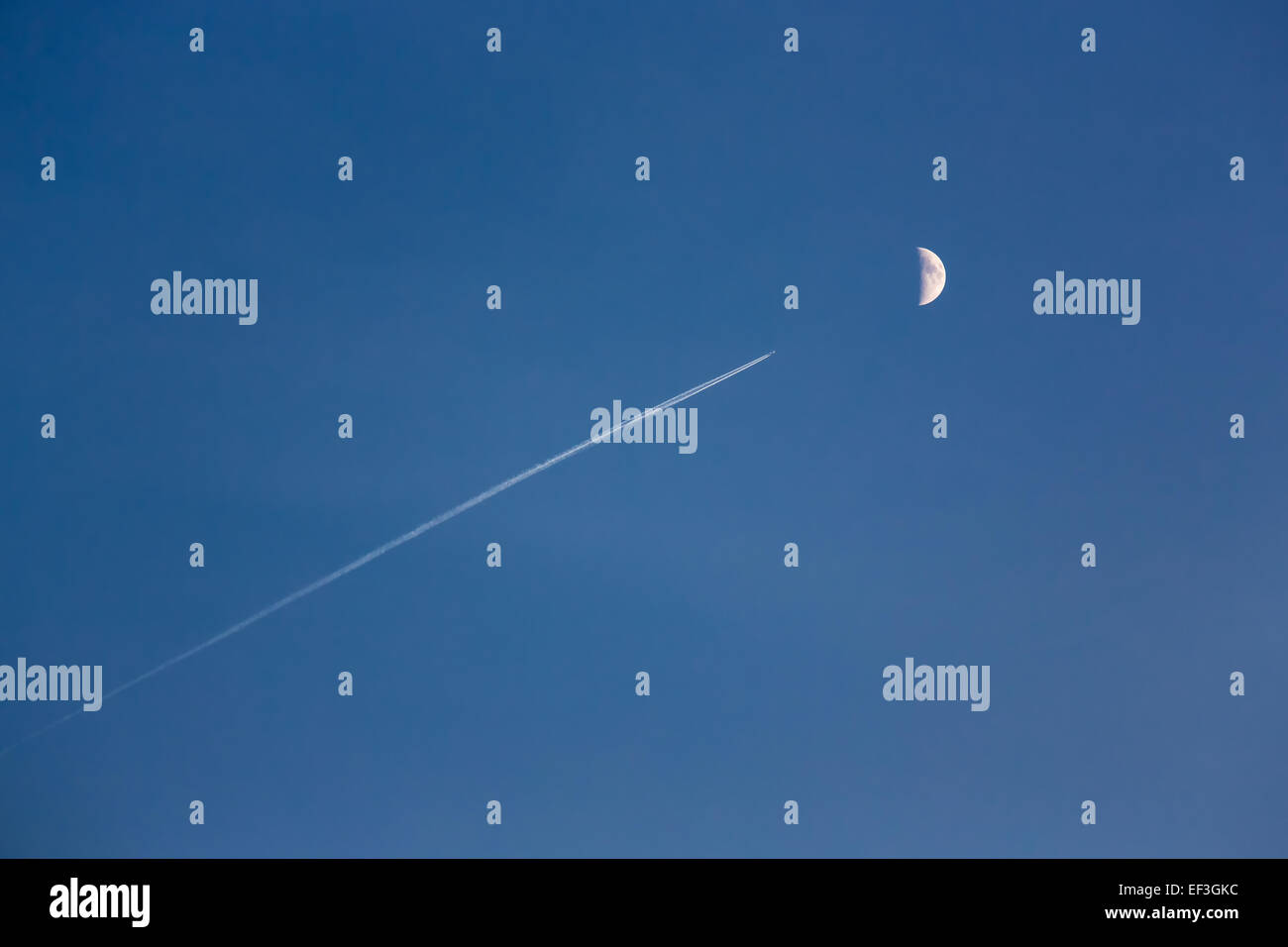 Trace of the jet plane in the blue sky with the moon on a background - Stock Image