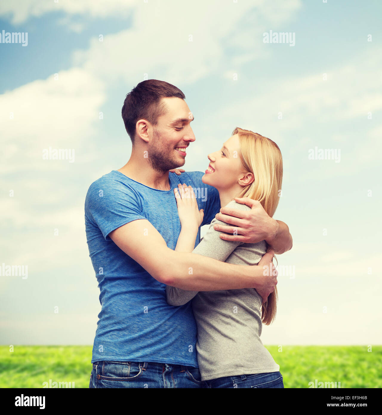 smiling couple hugging and looking at each other - Stock Image