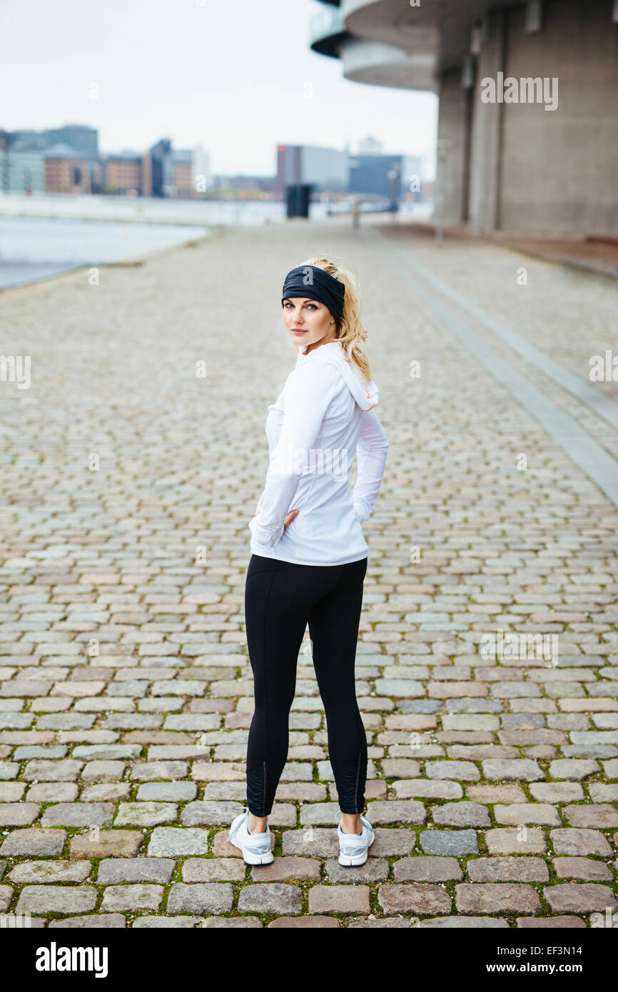 Outdoor shot of young woman standing on sidewalk looking over shoulder. Fitness female model ready for a city run. - Stock Image