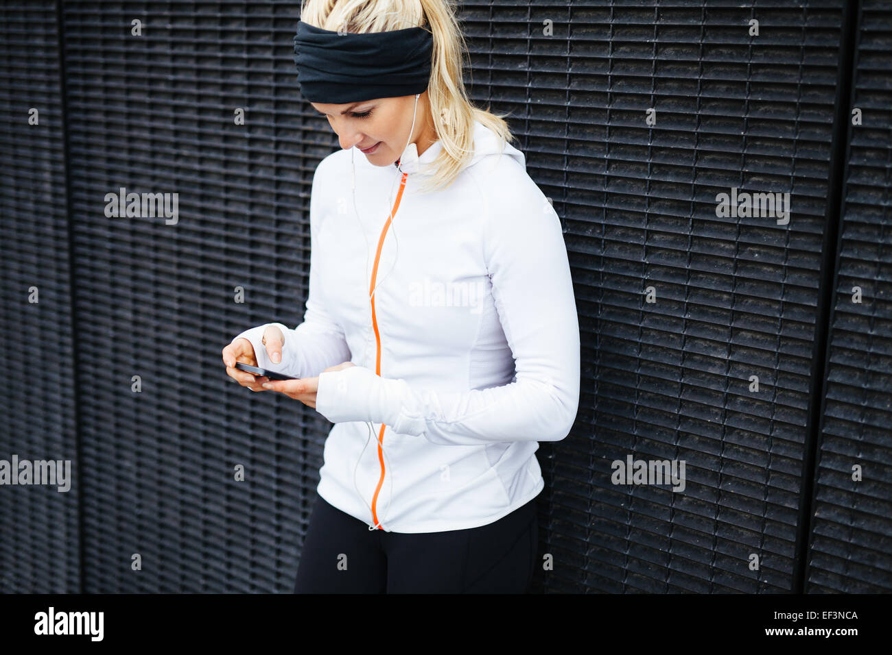 Image of young woman taking a break form workout using mobile phone outdoors. - Stock Image