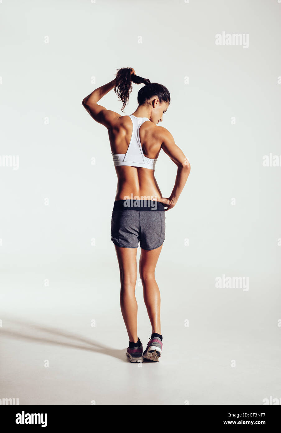 Rear view of a slim and fit young woman in sportswear holding her hair. Muscular female model standing on grey background. - Stock Image