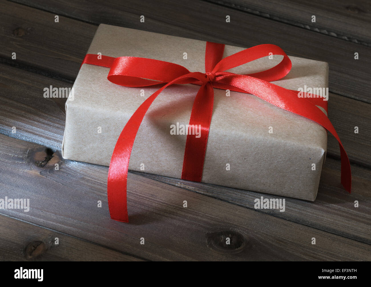 Vintage gift box wrapped in kraft paper on wooden background Stock Photo