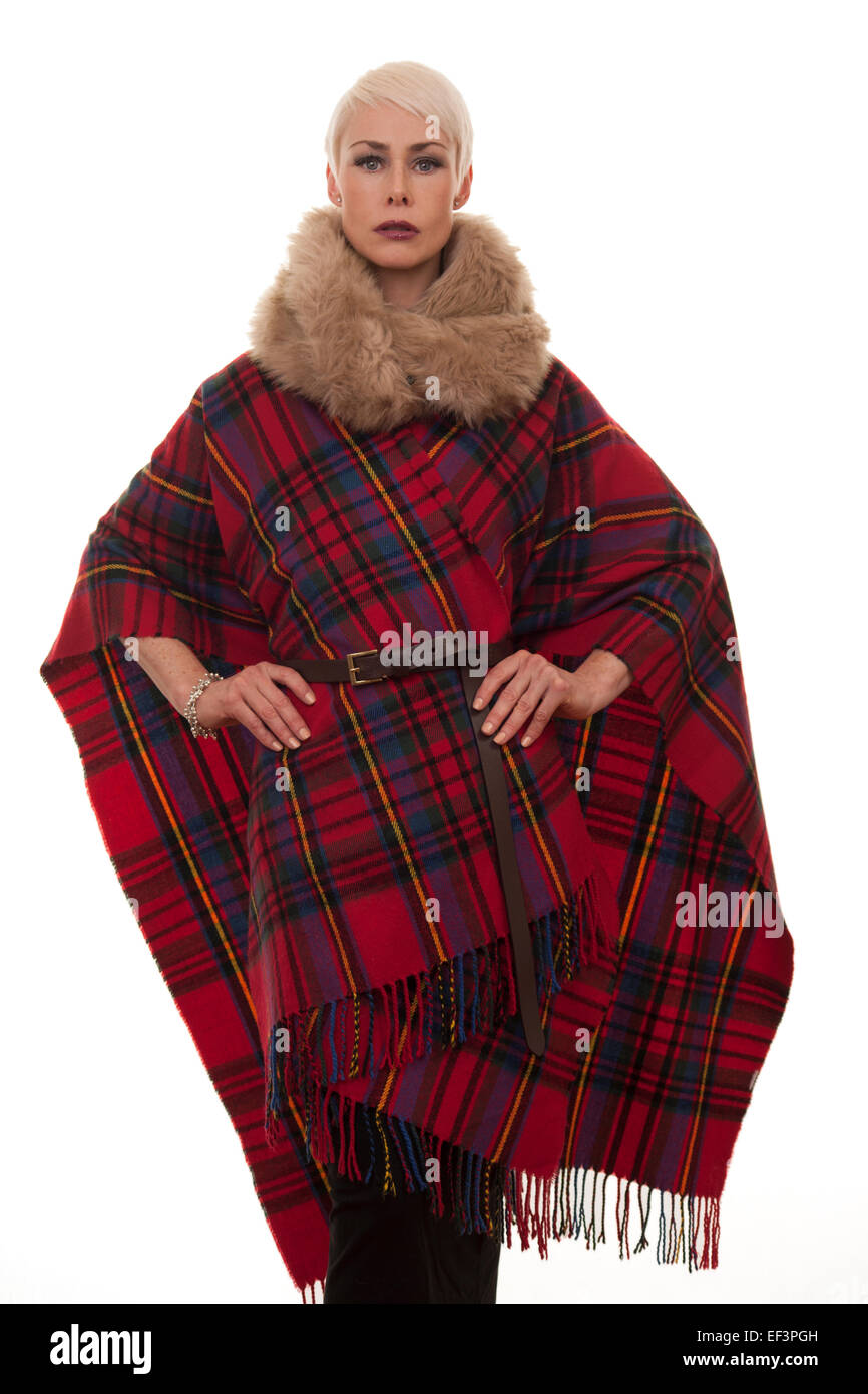 mature woman wearing a tartan blanket cape to keep warm - Stock Image