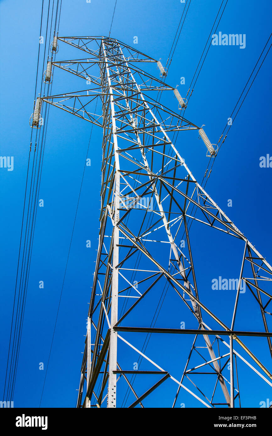 An electricity pylon against a cloudless blue sky. - Stock Image